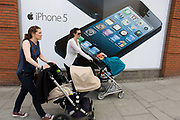 Two mothers pushing their baby's buggies, walk past a large poster for the iPhone 5 on the wall of a 'Carphone Warehouse' retailer. With the large image of its screen of this popular smartphone over their shoulders, the ladies make their way uphill in Wimbledon, London, passing this store selling Apple and other brands for consumers.