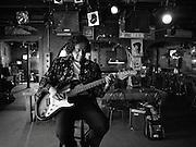 "Blues guitarist Beverly ""Guitar"" Watkins plays her electric guitar in a tavern."