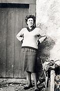 woman standing by old wooden door France ca 1960s