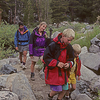 A family hikes down a trail during a rainy afternoon in California's eastern Sierra Nevada.