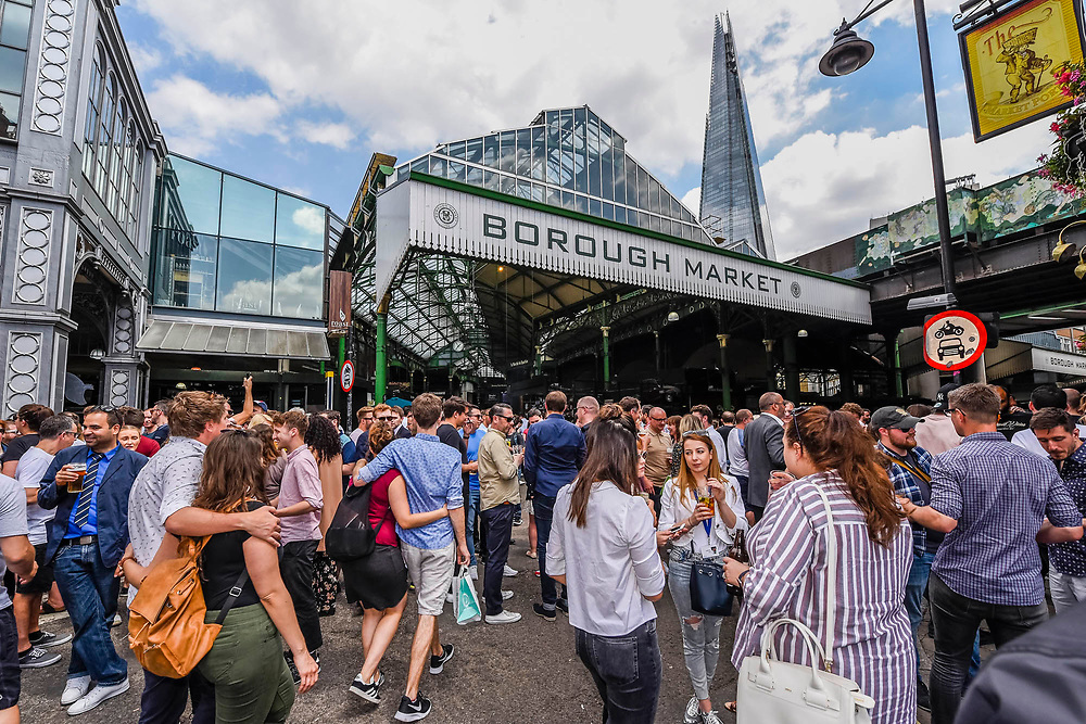 Couples go arm in arm and Stoney street is soon thronging with lunchtime eaters and drinkers - The market reopening is signified by the ringing of the bell and is attended by Mayor Sadiq Khan. Tourists and locals soon flood back to bring the area back to life. London  14 June 2017.
