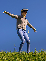 Girl wearing virtual reality headset with arms outstretched on grass field