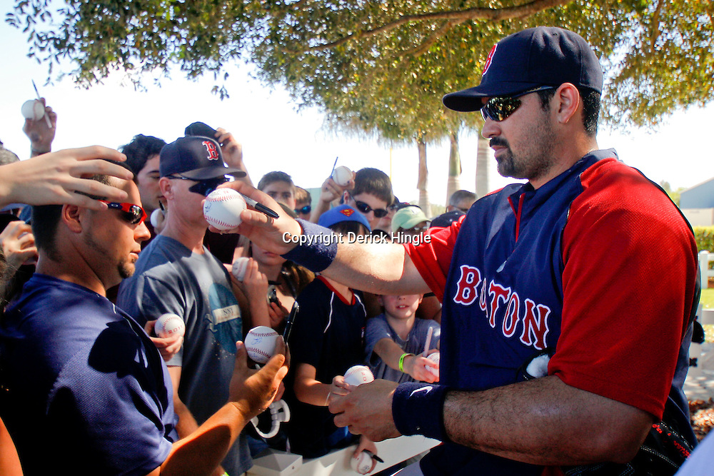 February 23, 2011; Fort Myers, FL, USA; Boston Red Sox first baseman Adrian Gonzalez (28) signs autographs for fans following a spring training practice at the Player Development Complex.  Mandatory Credit: Derick E. Hingle
