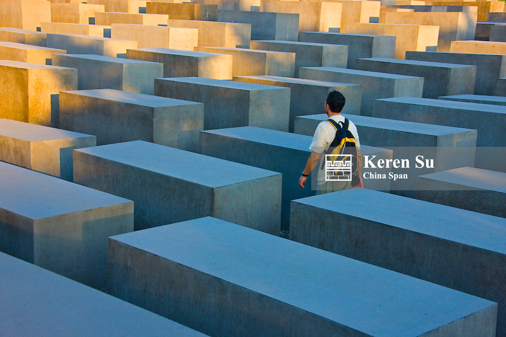 Tourist in Holocaust Memorial, concrete cubes, Berlin, Germany