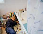 Plumber Pauline Brown in a flat conversion..Pauline Brown lies across the floor in a converted Hackney council flat bathroom... .