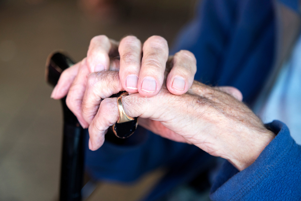 hands of an elderly man resting on his walking stick