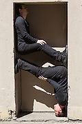 Twoo performers braced in a doorway, part of the Ideas City street fesival. Otehr performances included dance and music.