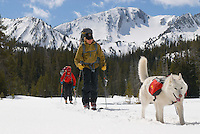 A young couple ski tours in the backcountry of the Wallowa Mountains.  Eagle Cap Wilderness Area, Oregon.