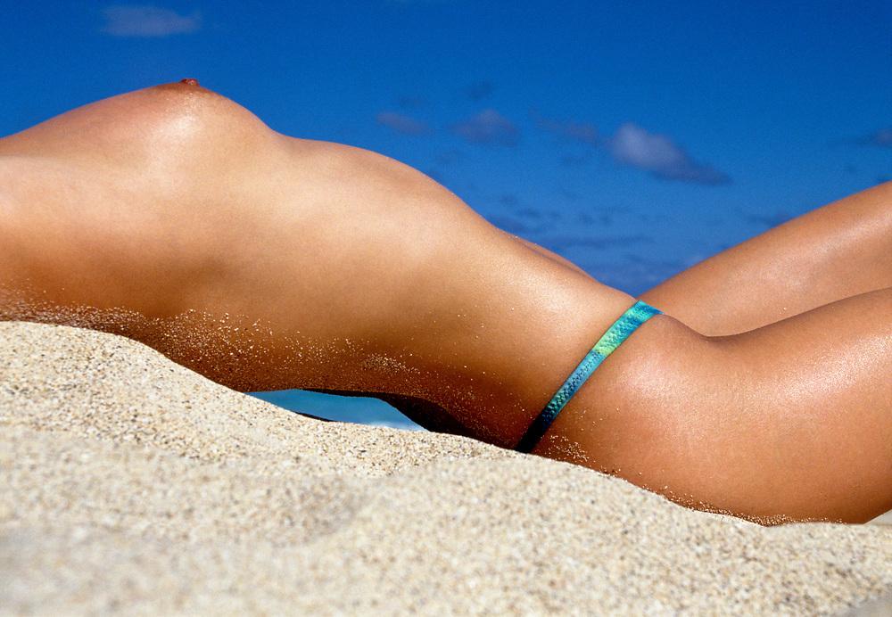 Profile of woman sunbathing on sand dune with blue sky