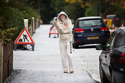 © Licensed to London News Pictures . 09/11/2013 . Manchester , UK . Undeterred , a man takes a cigarette break wearing open-toed sandles on the hailstones on a street in Salford . A freak hail storm in Manchester covers the streets with large hailstones as loud rolling thunder is heard . Photo credit : Joel Goodman/LNP