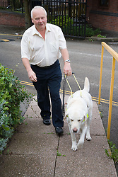 Man with his guide dog visiting the Nottingham Royal Society for the Blind (NRSB),