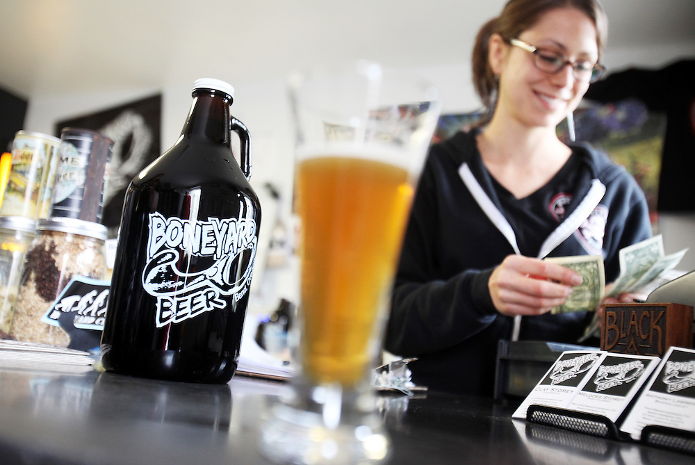 Alison Wood collects cash in exchange for a growler at Boneyard Brewing. Craft beer permeates the culture in Central Oregon city of Bend, with 10 breweries serving pints, growlers and kegs to a community of less than 90,000. Photographed Wednesday, April 25, 2012. Assignment ID 30125094A