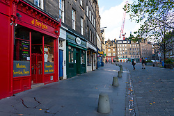 Edinburgh,Scotland, UK. 30 October 2020. With Edinburgh remaining in Tier 3 (Level 3) lockdown bars and restaurants remain severely restricted in business hours with many remaining closed and boarded up.  Pictured; Cafes and bars on Grassmarket are closed and few people are about on the normal busy square. Iain Masterton/Alamy Live News