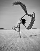 Black and white photo of a nude woman waving a long scarf at the Bonneville Salt Flats, Utah