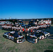 Legendary Race Car Driver Dale Earnhardt and his support team at company headquarters.  Dale is in behind the car on the left