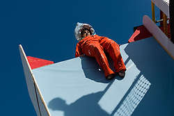 © Licensed to London News Pictures. 25/06/2015. Pilton, UK. A festival goer slides down a vertical slide in the Greenpeace field at Glastonbury Festival 2015 on Thursday Day 2 of the festival.  This years headline acts include Kanye West, The Who and Florence and the Machine, the latter having been upgraded in the bill to replace original headline act Foo Fighters.   Photo credit: Richard Isaac/LNP