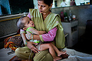 Aliyar, 18 months, a boy suffering from a severe case of hydrocephalus, is lying in the arms of his mother, Roxana, 31, inside the Bhopal Memorial Hospital and Research Centre, Madhya Pradesh, India.
