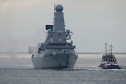 © Licensed to London News Pictures. 28/10/2016. Portsmouth, UK.  A puff of smoke blasts out of the starboard side of the Royal Navy Type 45 Destroyer HMS Diamond performs a seventeen-gun salute as she returns to Portsmouth. The Portsmouth-based Destroyer has completed her two month operation countering the illegal arms trade into Libya and has now handed over duties in the Central Mediterranean Sea to another Royal Navy ship, RFA Mounts Bay.  Photo credit: Rob Arnold/LNP
