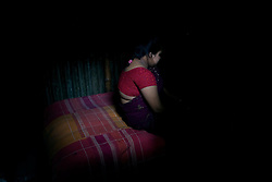 Sex worker Munnie, 15, sinks in after a service during which a customer beat her at brothel in Tangail, Bangladesh.