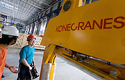 Kone Cranes Electric Site Supervisor PU Jian (left) speaks with Kone Cranes' Automation Designer Minh KY (center) about operating an Heavy Duty Semi-Automatic 60 + 60 ton Kone Crane in Oji Paper Factory, in Nantong, Jiangsu province, China, on May 25, 2010. Photo by Lucas Schifres/Pictobank