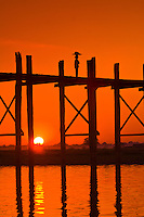 A woman in silhouette walking over the U-Bein Bridge (longest teak wood bridge in the world), Amarapura, Burma (Myanmar)