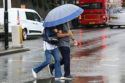 © Licensed to London News Pictures. 19/07/2019. London, UK. People shelter from the rain beneath an umbrella in north London. Photo credit: Dinendra Haria/LNP