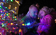 Shaun Mallet holds his daughter, Trinity beside the Christmas tree after the annual Christkindlmarket lantern parade and Christmas tree lighting ceremony at This Is The Place Heritage Park, Thursday, Nov. 29, 2012.