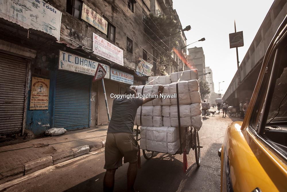 2014 10 29  Kolkata Calcutta <br /> West Bengal India Indien<br /> MG roads<br /> Man som puttar en full lastad cykelkärra<br /> <br /> <br /> ----<br /> FOTO : JOACHIM NYWALL KOD 0708840825_1<br /> COPYRIGHT JOACHIM NYWALL<br /> <br /> ***BETALBILD***<br /> Redovisas till <br /> NYWALL MEDIA AB<br /> Strandgatan 30<br /> 461 31 Trollhättan<br /> Prislista enl BLF , om inget annat avtalas.