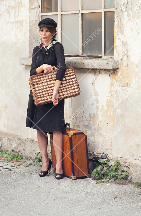 Woman waiting in the street with luggage