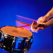 Drummers blurred hands and drumsticks on drum.<br /> Cymbal with blue background.
