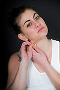 Young Woman pinching her neck. She may be keeping track of weight loss during a diet but compulsive body analysis may be a symptom of a body image disorder such as anorexia nervosa. Model released