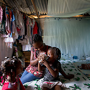 Margarita gives water to one of her seven children, in the bedroom of their home in the la Cubana area of San Pedro Province in the Dominican Republic, September 12, 2017. The area was not badly hit by Hurricane Irma, though it is prone to diseases, especially now in the rainy season with increased rainfall during the hurricane. Several areas with stagnant water are breeding grounds for mosquitos, increasing cases of dengue, chikungunya, zika and others. stands with two of her seven children in front of their house in the la Cubana area of San Pedro Province in the Dominican Republic, September 12, 2017. The area was not badly hit by Hurricane Irma, though it is prone to diseases, especially now in the rainy season with increased rainfall during the hurricane. Several areas with stagnant water are breeding grounds for mosquitos, increasing cases of dengue, chikungunya, zika and others. The only drinking water available is bought, consuming a large percentage of their weekly budget.