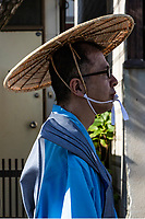 Shinto Priest at Mengake Procession - Mengake or Masked Parade at Goryo Jinja shrine.  At this festival held in September a group of ten people take part in this annual ritual: 8 men and 2 women. Wearing comical or grotesque masks that signify different demons, legends and dieties  leave the shrine and parade through the nearby streets accompanied by portable shrine and festival music.