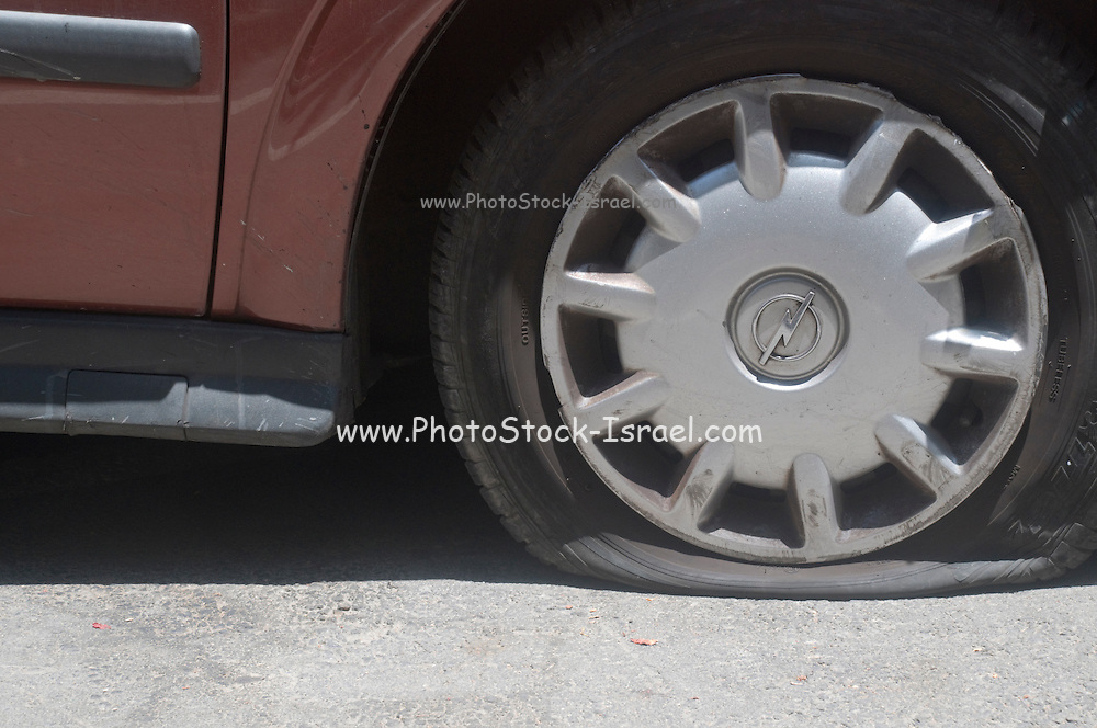 A vandalised car, two punctured tires and scratche along the side of the car on on the hood