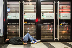 © Licensed to London News Pictures . 01/01/2014 . Manchester , UK . A man lies collapsed in a shop doorway . Revellers see in the New Year in Manchester today (January 1st 2014) as police report that officers are at full stretch responding to calls . Photo credit : Joel Goodman/LNP