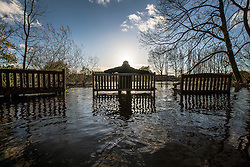 © Licensed to London News Pictures. 19/11/2015. Boroughbridge UK. A man sits on a half submerged park bench in a flooded park in the Centre of Boroughbridge in Yorkshire. The Environment Agency have issued 12 flood alerts for the county & more flooding is expected.Photo credit: Andrew McCaren/LNP