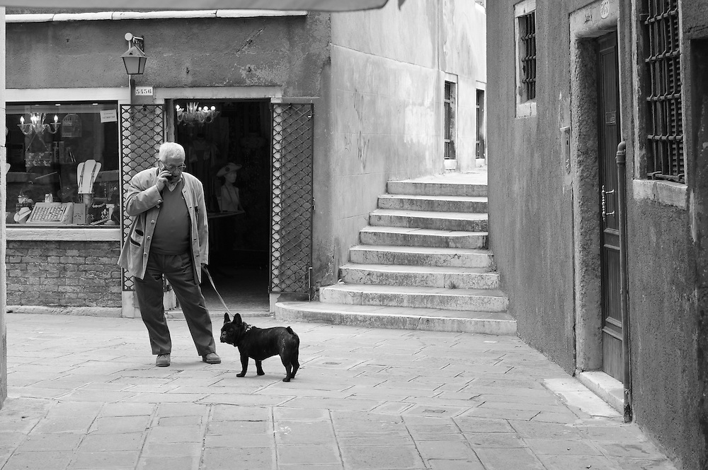 Man talking on the phone whilst walking his dog.