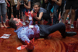 Two environmental activists from Extinction Rebellion, one dressed as a financier, cover themselves in fake blood during a mass civil disobedience event in Paternoster Square following a Blood Money March through the City of London on 27th August 2021 in London, United Kingdom. Extinction Rebellion were intending to highlight financial institutions funding fossil fuel projects, especially in the Global South, as well as law firms and institutions which facilitate them, whilst calling on the UK government to cease all new fossil fuel investment with immediate effect.