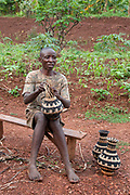 Rwanda February 2014. Kigali. Rutongo. Jari secteur, Nyamitanga cellule.  A barefooted man sits on a bench making a vase from banana leaves.