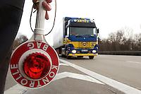 03 JAN 2005, LUDWIGSFELDE/GERMANY:<br /> Beamter des Bundesamtes fuer Gueterverkehr mit Kelle, waehrend einer Mautkontrolle, Parkplatz Fresdorfer Heide<br /> IMAGE: 20050103-01-007<br /> KEYWORDS: Bundesamt für Güterverkehr, LKW Maut, Kontroleur<br /> BAG