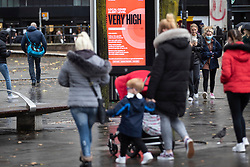 © Licensed to London News Pictures. 31/10/2020. Manchester, UK. A family walk past a Very High Risk sign in Manchester. The wet weather and tier 3 restrictions don't deter some people in Manchester today. Photo credit: Kerry Elsworth/LNP