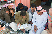 Middle East, Hashemite Kingdom of Jordan, Aqaba Governorate, the highland mountains a group of local Bedouins and a Caucasian tourist reading a book