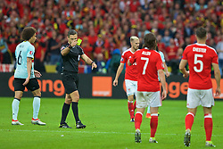 LILLE, FRANCE - Friday, July 1, 2016: Wales' Joe Allen is shown a yellow card by referee Damir Skomina during the UEFA Euro 2016 Championship Quarter-Final match against Belgium at the Stade Pierre Mauroy. (Pic by Paul Greenwood/Propaganda)