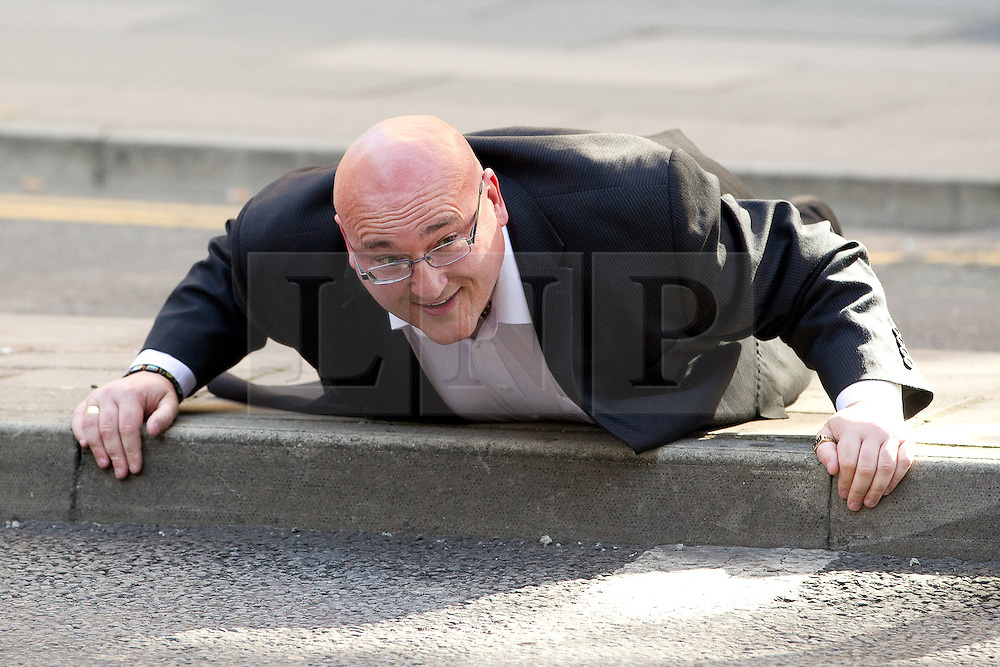 © Licensed to London News Pictures .  08/09/2012 . Manchester, UK . Domenyk Noonan , recently released from prison , lies face down on a traffic island on Aytoun Street in Manchester, recreating the moment when he was detained with members of his gang , at the same spot in Manchester City Centre , on 9th August 2011 , during a night of riots and looting in the city . The area was the scene of looting and rioting on 9th August 2011 , during which Noonan was arrested . Noonan has announced he plans to sue the police over the  arrest . Under the terms of a previous early release , the arrest lead to him being recalled to prison . Photo credit : Joel Goodman/LNP