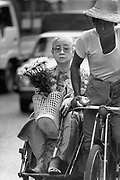 Woman clutching a shopping basket and a bunch of flowers travel by cycle rickshaw. Rangoon, Burma 1999