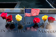 New York, NY - 10 September 2021. Official and private memorials are held at the 9/11 memorial site on the day before the 20th anniversary of the World Trade Center attacks. Red and yellow roses and a small American flag in the name of Donna Marie Clarke on the bronze parapet of the memorial wall.