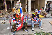 17 JANUARY 2014 - BANGKOK, THAILAND: Anti-government protestors take a break while searching for assailants who threw small IEDs at them during a protest march in Bangkok. The attackers were not found but officials claim to have found a weapons cache in an abandoned building nearby. Friday was day 5 of the anti-government Shutdown Bangkok protests. The protest, led by the People's Democratic Reform Committee, is calling for the suspension of elections pending political reform in Thailand. There was violence at several sites in Bangkok Friday, including running battles between government opponents and supporters at one site and an IED attack by unknown assailants on anti-government protestors at another site.    PHOTO BY JACK KURTZ