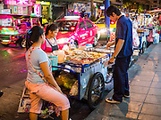 """27 MARCH 2013 - BANGKOK, THAILAND:  A man looks at grilled meat for sale on a street food cart in a tourist district in Bangkok. Thailand's economic expansion since the 1970 has dramatically reduced both the amount of poverty and the severity of poverty in Thailand. At the same time, the gap between the very rich in Thailand and the very poor has grown so that income disparity is greater now than it was in 1970. Thailand scores .42 on the """"Ginni Index"""" which measures income disparity on a scale of 0 (perfect income equality) to 1 (absolute inequality in which one person owns everything). Sweden has the best Ginni score (.23), Thailand's score is slightly better than the US score of .45.  PHOTO BY JACK KURTZ"""