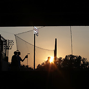 Fans walk past the netting behind home plate as the sun sets during the New Britain Rock Cats Vs Binghamton Mets Minor League Baseball game at New Britain Stadium, New Britain, Connecticut, USA. 2nd July 2014. Photo Tim Clayton
