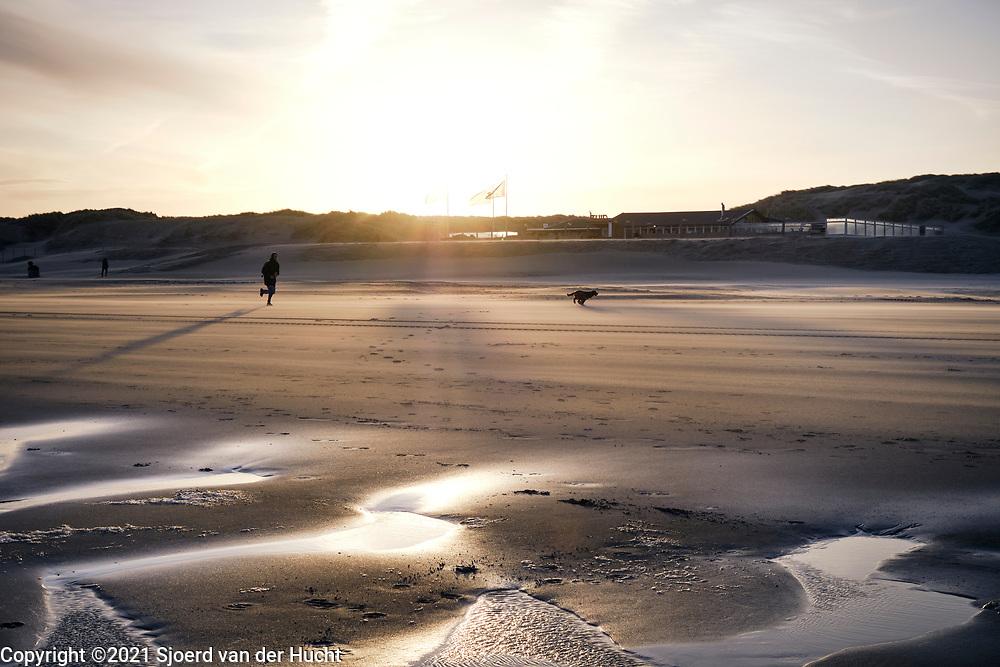 Rennen met de hond in de ochtend op het Zuiderstrand in Den Haag.    Run with the dog in the morning on Southbeach,  The Hague.